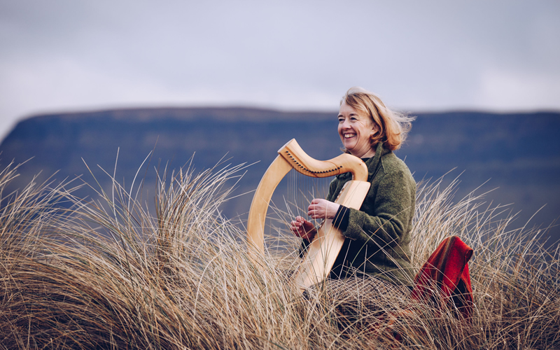 Celia playing harp in front of Benbulben